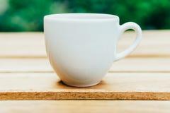 Άσπρο φλυτζάνι καφέ στον ξύλινο πίνακα στον κήπο Στοκ φωτογραφία με δικαίωμα ελεύθερης χρήσης