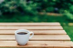 Άσπρο φλυτζάνι καφέ στον ξύλινο πίνακα στον κήπο Στοκ φωτογραφίες με δικαίωμα ελεύθερης χρήσης
