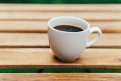 Άσπρο φλυτζάνι καφέ στον ξύλινο πίνακα στον κήπο Στοκ εικόνα με δικαίωμα ελεύθερης χρήσης