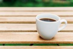 Άσπρο φλυτζάνι καφέ στον ξύλινο πίνακα στον κήπο Στοκ Εικόνες