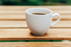 Άσπρο φλυτζάνι καφέ στον ξύλινο πίνακα στον κήπο Στοκ Εικόνα