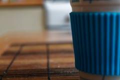 Άσπρο φλυτζάνι με την μπλε στάση κατόχων φλυτζανιών στον πίνακα Στοκ φωτογραφίες με δικαίωμα ελεύθερης χρήσης