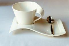 Άσπρο φλυτζάνι σχεδιαστών σε ένα πιατάκι με ένα κουταλάκι του γλυκού Στοκ Φωτογραφία