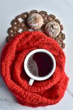 Άσπρο φλυτζάνι του καυτού μαύρου καφέ και των γλυκών μπισκότων με το κόκκινο πλεκτό ύφασμα στοκ εικόνα