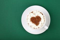 Άσπρο φλυτζάνι του καφέ cappuccino στο πιατάκι σε πράσινο Στοκ Φωτογραφίες