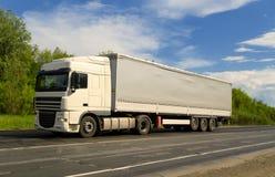Άσπρο φορτηγό στο δρόμο ασφάλτου κάτω από το μπλε ουρανό με τα σύννεφα Στοκ Εικόνες