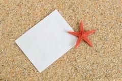Άσπρο φύλλο στην άμμο και τον αστερία Στοκ Φωτογραφίες