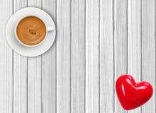 Άσπρο φλιτζάνι του καφέ και κόκκινη καρδιά σε ξύλινο Στοκ Φωτογραφία