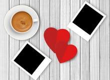 Άσπρο φλιτζάνι του καφέ, κόκκινες καρδιές και φωτογραφία σε ξύλινο Στοκ εικόνα με δικαίωμα ελεύθερης χρήσης