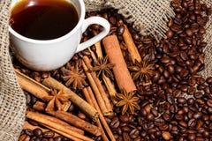 Άσπρο φλιτζάνι του καφέ σε ένα υπόβαθρο του ξύλου και burlap, που περιβάλλεται από τα σιτάρια καφέ και κανέλας Στοκ Εικόνα