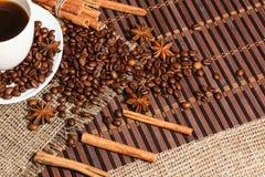Άσπρο φλιτζάνι του καφέ σε ένα υπόβαθρο του ξύλου και burlap, που περιβάλλεται από τα σιτάρια καφέ και κανέλας Στοκ φωτογραφία με δικαίωμα ελεύθερης χρήσης