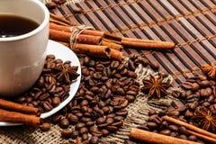 Άσπρο φλιτζάνι του καφέ σε ένα υπόβαθρο του ξύλου και burlap, που περιβάλλεται από τα σιτάρια καφέ και κανέλας Στοκ Φωτογραφία