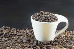 Άσπρο φλυτζάνι καφέ που γεμίζουν με τα φασόλια καφέ που τοποθετούνται ψημένος coff Στοκ εικόνα με δικαίωμα ελεύθερης χρήσης