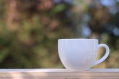 Άσπρο φλυτζάνι καφέ στον κήπο πράσινο στοκ εικόνα με δικαίωμα ελεύθερης χρήσης