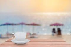 Άσπρο φλυτζάνι καφέ στον ξύλινο πίνακα με την παραλία β θάλασσας τοπίου θαμπάδων Στοκ εικόνα με δικαίωμα ελεύθερης χρήσης