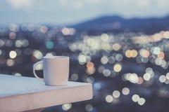 Άσπρο φλυτζάνι καφέ στο αντίθετο και ζωηρόχρωμο φως θαμπάδων bokeh cit Στοκ Εικόνες