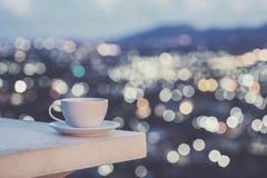 Άσπρο φλυτζάνι καφέ στο αντίθετο και ζωηρόχρωμο φως θαμπάδων bokeh cit Στοκ Εικόνα
