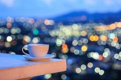Άσπρο φλυτζάνι καφέ στο αντίθετο και ζωηρόχρωμο φως θαμπάδων bokeh cit Στοκ Φωτογραφία