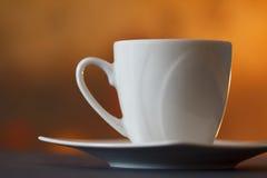 Άσπρο φλυτζάνι καφέ στο αφηρημένο υπόβαθρο θαμπάδων Στοκ Εικόνες
