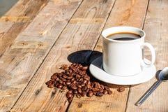 Άσπρο φλυτζάνι καφέ στο ξύλινο επιτραπέζιο υπόβαθρο με τη σκιά από το φως του ήλιου Στοκ εικόνα με δικαίωμα ελεύθερης χρήσης