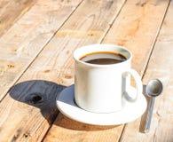 Άσπρο φλυτζάνι καφέ στο ξύλινο επιτραπέζιο υπόβαθρο Στοκ Φωτογραφία