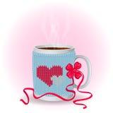 Άσπρο φλυτζάνι με μια μπλε πλεκτή κάλυψη Στο σχέδιο κάλυψης με δύο κόκκινες και άσπρες καρδιές και με το κόκκινο τόξο ποτό ζεστό  Στοκ Εικόνες