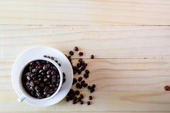 Άσπρο φλυτζάνι με τα σιτάρια καφέ ξύλινο table-top Στοκ εικόνα με δικαίωμα ελεύθερης χρήσης
