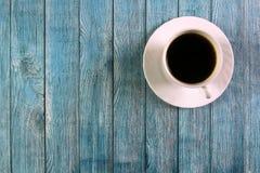 Άσπρο φλυτζάνι με το μαύρο καφέ σε ένα μπλε ξύλινο υπόβαθρο στοκ φωτογραφίες