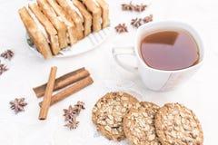 Άσπρο φλυτζάνι με το τσάι, σπιτικά μπισκότα με τα δημητριακά, βιενέζικες βάφλες με την πλήρωση κρέμας, ραβδιά κανέλας, αστέρια γλ Στοκ Φωτογραφία