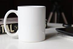 Άσπρο φλυτζάνι σε έναν πίνακα Στοκ Φωτογραφίες
