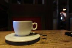 Άσπρο φλυτζάνι σε έναν σκοτεινό καφέ Στοκ εικόνα με δικαίωμα ελεύθερης χρήσης