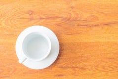 Άσπρο φλυτζάνι στο ξύλινο επιτραπέζιο υπόβαθρο Στοκ Εικόνες