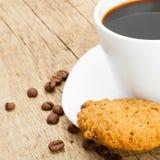 Άσπρο φλυτζάνι του σαφούς μαύρου καφέ με τα μπισκότα δίπλα σε το - κλείστε αυξημένος στοκ εικόνες