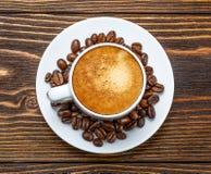 Άσπρο φλυτζάνι του espresso σε ένα ξύλινο υπόβαθρο Στοκ Φωτογραφία
