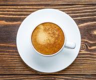 Άσπρο φλυτζάνι του espresso σε ένα ξύλινο υπόβαθρο Στοκ Εικόνες