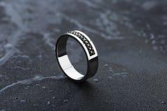 Άσπρο χρυσό γαμήλιο δαχτυλίδι με τους μαύρους πολύτιμους λίθους στο μαύρο υπόβαθρο στοκ εικόνες