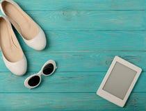 Άσπρο χρώμα παπουτσιών γυναικών ` s και γυαλιών ήλιων, ηλεκτρονικό βιβλίο στο α Στοκ φωτογραφία με δικαίωμα ελεύθερης χρήσης