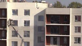 Άσπρο χρώμα ψεκασμού ατόμων ζωγράφων στο νέο επίπεδο τοίχο σπιτιών απόθεμα βίντεο