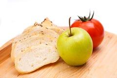 Άσπρο ψωμί με τα φασόλια, ντομάτα, Apple σε έναν ξύλινο δίσκο Στοκ Εικόνα