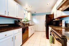 Άσπρο δωμάτιο κουζινών με τις μαύρες συσκευές Στοκ Εικόνες