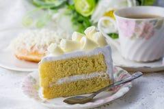 Άσπρο όμορφο φλυτζάνι κέικ choclate wiyh του coffe στον άσπρους πίνακα και το λουλούδι Στοκ Φωτογραφίες