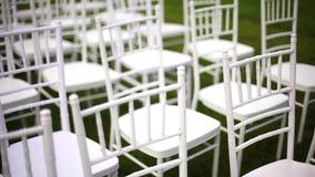Άσπρο chiavari γαμήλιων καρεκλών σε έναν πράσινο χορτοτάπητα, χωρίς διακόσμηση απόθεμα βίντεο