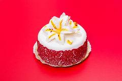 Άσπρο fondant κέικ που διακοσμείται με την κόκκινη δαντέλλα και τον εδώδιμο κρίνο καραμελών Στοκ Φωτογραφία