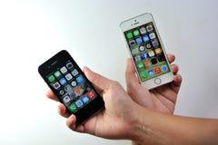 Άσπρο iPhone της Apple 5S & μαύρο iPhone της Apple 4S Στοκ Εικόνες