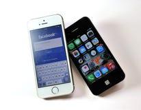 Άσπρο iPhone της Apple 5S & μαύρο iPhone της Apple 4S Στοκ φωτογραφίες με δικαίωμα ελεύθερης χρήσης