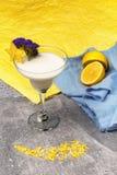 Άσπρο milkshake σε ένα ζωηρόχρωμο υπόβαθρο Ένα γυαλί ενός κουνήματος βανίλιας με τα λεμόνια και τα λουλούδια και το carambola ανα Στοκ Φωτογραφία