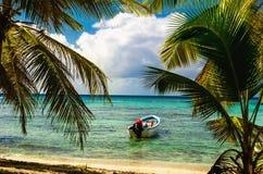 Άσπρο motorboat έδεσε στην εξωτική ακτή με τους όμορφους καταπληκτικούς φοίνικες που εισάγουν τη θάλασσα, Δομινικανή Δημοκρατία στοκ εικόνες