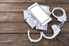 Άσπρο smartphone στα τραπεζογραμμάτια με τις χειροπέδες σε ένα ξύλινο υπόβαθρο στοκ εικόνες με δικαίωμα ελεύθερης χρήσης