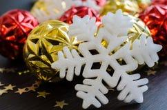 Άσπρο snowflake στο υπόβαθρο των κόκκινων και χρυσών μπιχλιμπιδιών Χριστουγέννων Στοκ Φωτογραφίες