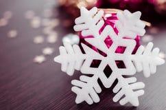 Άσπρο snowflake στο υπόβαθρο των ροδανιλίνης και χρυσών μπιχλιμπιδιών Χριστουγέννων Στοκ Φωτογραφία